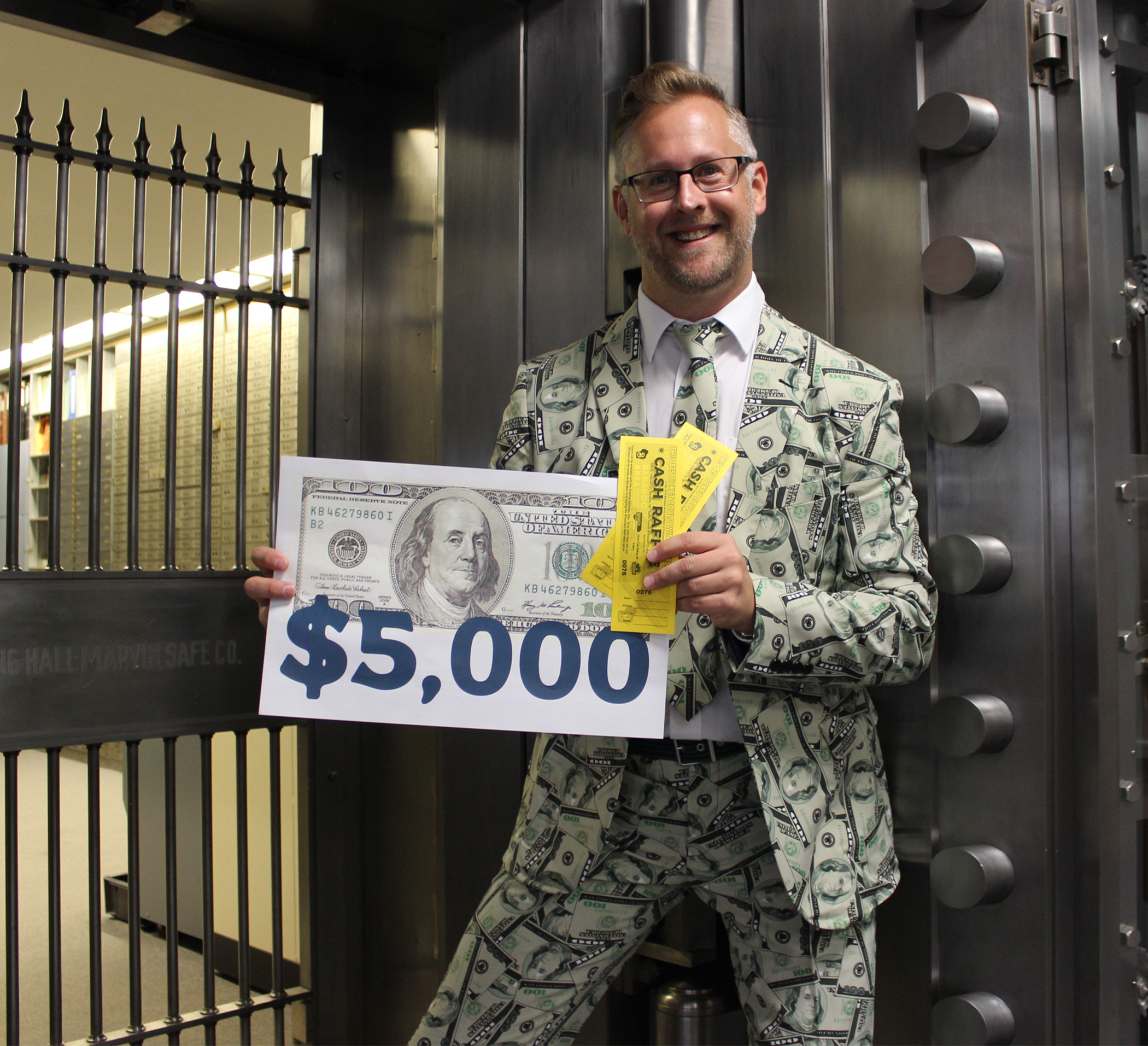 Chamber executive wearing cash suit outside bank vault
